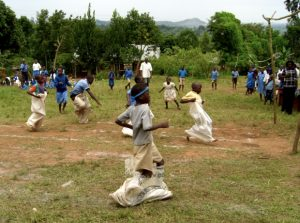 Children at a primary school in Uganda playing games in their first ever sports day organised by volunteers.